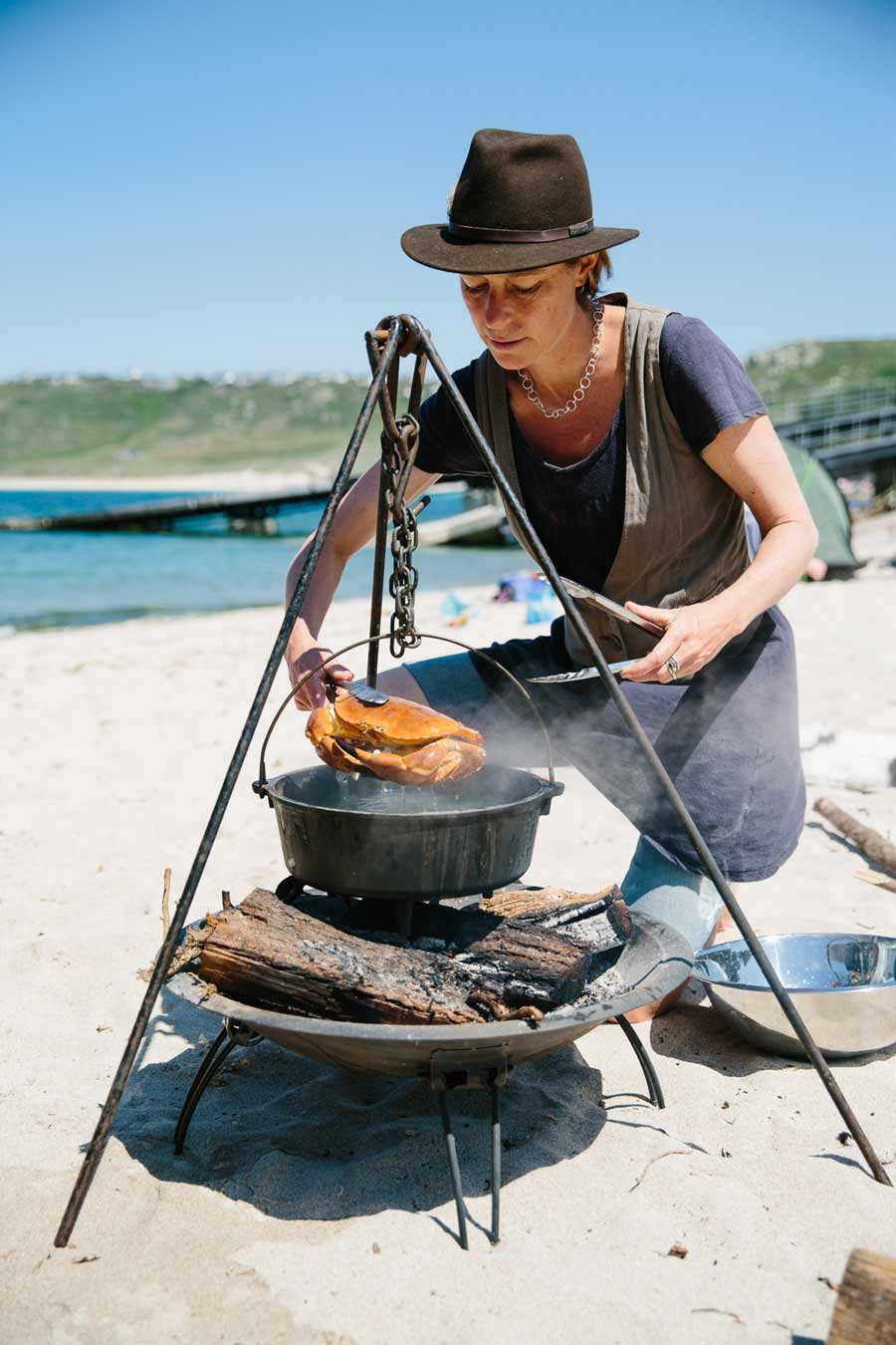 Photograph of Caroline Davey from Fat Hen cooking crab on the beach